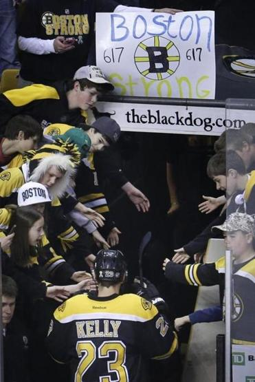 Fans held a homemade sign as Bruins center Chris Kelly stepped off the ice in April.