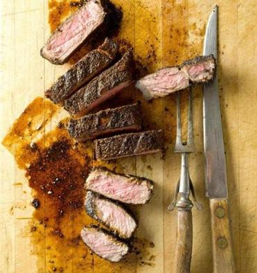 Rub New York strip steak with ground coffee and spices before grilling.