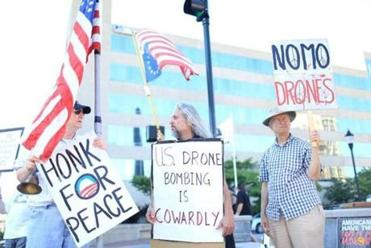 At left, Holland Quinby, Paul Turner, and Chris Berg held a Veterans for Peace vigil in liberal Asheville, N.C.