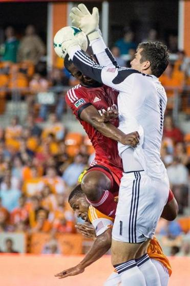 Dynamo goalkeeper Tally Hall (right) knocks the ball away from Toronto's Doneil Henry.