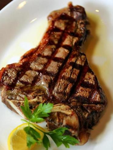 The bistecca Fiorentina at Toscano is 22 ounces of aged T-bone served with potatoes and spinach.