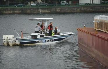 State Police in a boat in the Charles River inspected the fireworks barge.