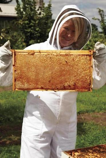 Martha Stewart in her one-piece bee-protective suit inspecting her hive.
