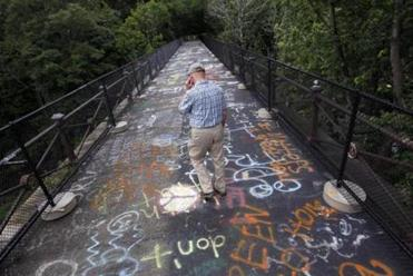 Vice Chair of Wellesley Trails Committee Denny Nackoney walks over the Waban Arches in Wellesley