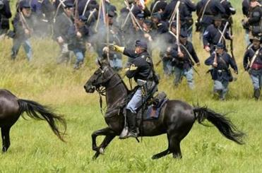 A Union cavalry reenactor exchanged fire with Confederate troops during a skirmish commemorating the 150th anniversary of the Battle of Gettysburg, a turning point in the Civil War.