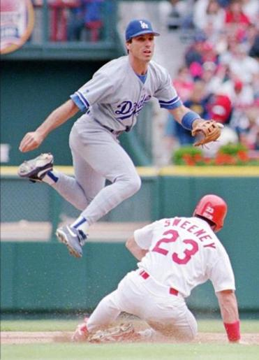 Los Angeles Dodgers shortstop Greg Gagne leapt over St. Louis Cardinals' Mark Sweeney on, May 12, 1996, in St. Louis.