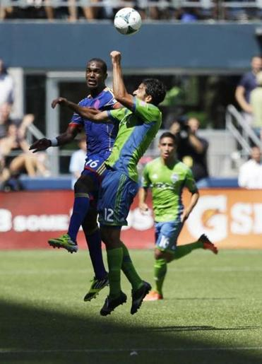 Seattle's Leo Gonzalez (12) goes up for a header against Colorado's Atiba Harris in the second half of a 1-1 tie.