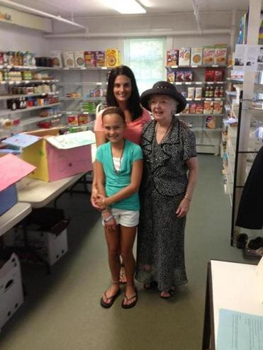 Riley Brennan, assisted by her mother, Carly, celebrates her 11th birthday by delivering canned food, paper goods and toiletry supplies — which she collected in lieu of gifts — to Holliston Pantry Shelf cofounder Sylvia Stickney.