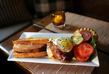 The Pineland Farm Beef Burger includes a fried egg, Applewood smoked bacon with charred red pnion, pickles, and sharp cheddar at The Winsor House in Duxbury.