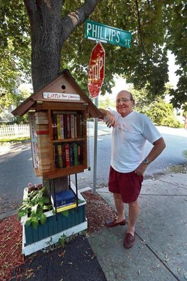 Howard Hashem visits the Little Free Library that he set up  under a maple tree in front of his Watertown home.