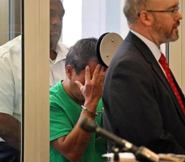 Steven Chan, a middle school teacher in Newton, shielded his face in Newton District Court during his arraignment on child pornography possession and dissemination charges. At right is his lawyer, Christopher Shannon.