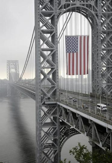 The largest free-flying American flag in the world flies over the George Washington Bridge under the upper arch of the bridge's New Jersey tower.