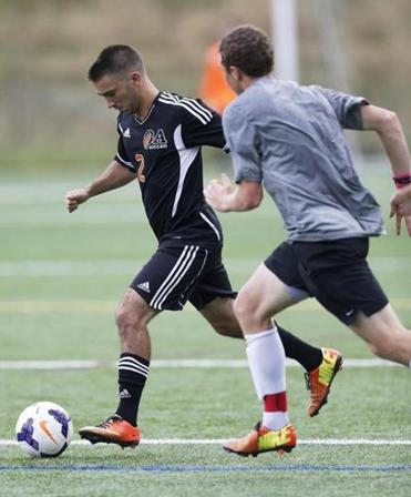 Oliver Ames midfielder Dave Stapleton carries the ball, as Concord-Carlisle's Mitchell Palmer gives chase.