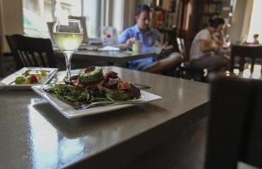 Roasted beet, arugula, and herbed chevre salad here is accompanied by the olive oil cake with lemon curd and glass of white wine.