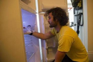 "Jack Goodman, a senior at Emerson College, looks inside his lightly stocked refrigerator. Goodman says, ""We have a kitchen, I just don't like to be in it."""