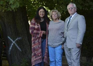Amy Glynn, Kate Brown, and lawyer Joseph Gregory stood by the tree they want protected.