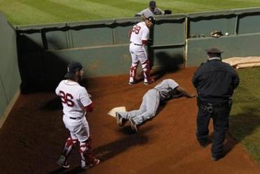 Tigers right fielder Torii Hunter gets attention from players and a policeman after falling hard into the Sox bullpen.