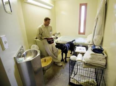 Inmate Edward Parent stood in his cell at a Cranston, R.I., prison with Chuck, a black lab he is training to be a service dog.