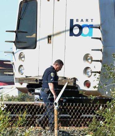 A police officer looked along the outside of a San Francisco commuter train that struck and killed two workers who were inspecting tracks over the weekend in Walnut Creek, Calif.