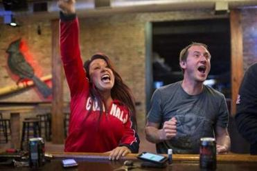 Marianna Avila and John Addison cheered on their team during the first game of the World Series on Wednesday at Paddy O's bar in St. Louis. The Series is knotted at 1-1.