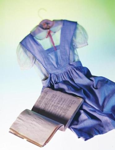 "A shooting script for ""The Wizard of Oz,"" with a dress tested by Judy Garland for the movie and the blouse she wore during the first two weeks of filming."