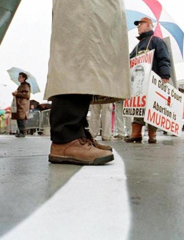 An escort for Planned Parenthood of Greater Boston kept her toes on a white line defining the 'buffer zone' as pro-life protesters gathered outside a clinic in Boston in 2000.