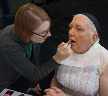 "Susanne Miller works omilln the makeup for Ed Peed for ""The Importance of Being Earnest."""