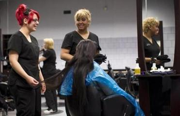Kaylee Cruz (left) and Irene Baez admire a client's hair at Greater Lowell Technical High School.