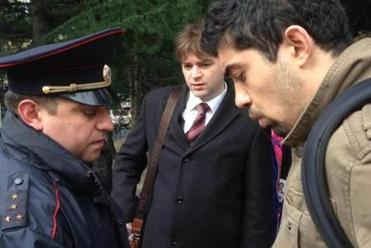 A Sochi police captain detains activist David Khakim while his lawyer Alexander Popkov looks on.