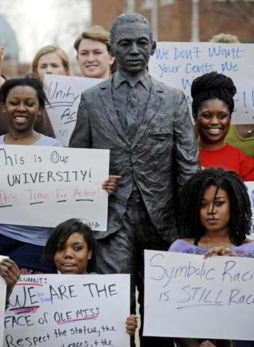 Students held signs in front of the James Meredith statue in Oxford. Miss.