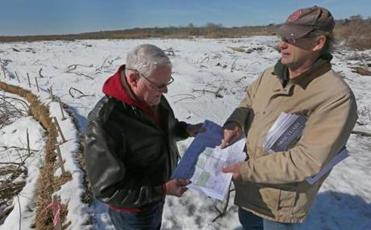 Residents Hugh Beagan and Joe Pecevich, who both question airport expansion, examine area maps
