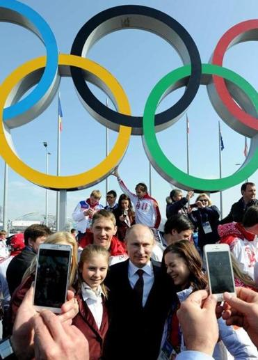 President Vladimir Putin with figure skaters Adelina Sotnikova (right) and Julia Lipnitskaya (left) after an award ceremony for Russian athletes Monday in Sochi.