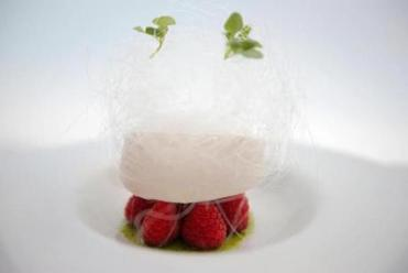 "A ""snow egg"" features a pillow of meringue atop raspberries with lemon curd mousse, basil syrup, and a crown of spun sugar."