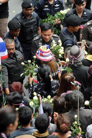 Antigovernment protesters presented roses to police as a sign of friendship during a rally in Bangkok Wednesday.