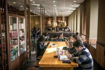 "Customers enjoy coffee and other drinks while working on their computers and iPads at a Starbucks in Seoul. ""At Starbucks, Koreans jumped on the bandwagon,"" a professor says."