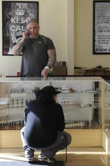 A customer browses while owner Mike Cook chats at Cumulus Vapors in Melrose.