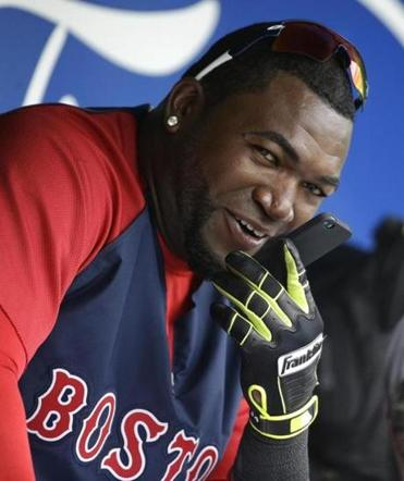 Boston Red Sox designated hitter David Ortiz speaks on a mobile phone in the dugout before an exhibition baseball game against the Atlanta Braves, Friday, March 7, 2014, in Fort, Myers, Fla. (AP Photo/Steven Senne)