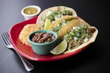 Beantown Taqueria in Cambridge makes carnitas tacos with braised pork, onions, and cilantro, with rice and beans.