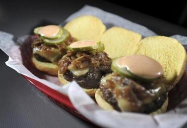 Three burgers topped with raclette, bacon-onion jam, pickles, and a tangy sauce.