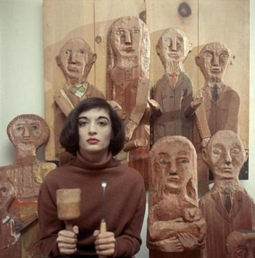 Marisol poses in 1958 in New York with her tools and some of her wooden sculptures.