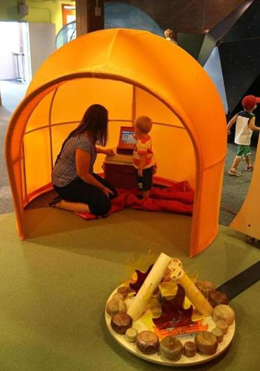 Allison Hersey and her son Jaelen, almost 2, from Portland, Maine, in an outdoor tent that is part of the exhibit.