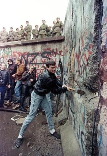 A demonstrator pounded away at the Berlin Wall as East Berlin border guards stood above the Brandenburg Gate on Nov. 11, 1989.