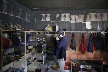 A man inspects damage on Nov. 30, in the aftermath of an arson attack that targeted first-grade classrooms at a bilingual Jewish-Arab school in Jerusalem.