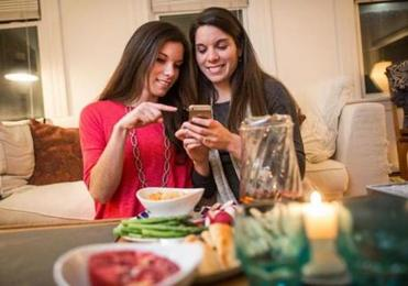 Blogging twin sisters  Marni (left) and Kara Powers taking an Instagram of a food setup at Marni's apartment in Cambridge.