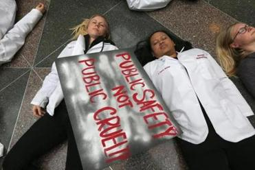 "Harvard Dental students Calie McCulloch (left) and Phianh Waldon participated in a ""die-in"" at Harvard Medical School's Tosteson Medical Education Center last week."