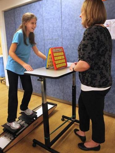Lucia Burillo Rojas, 11, with physical therapist Heather Molind, works out on a device that simulates skiing at Boston Children's at Waltham. (Wendy Maeda/Globe Staff)