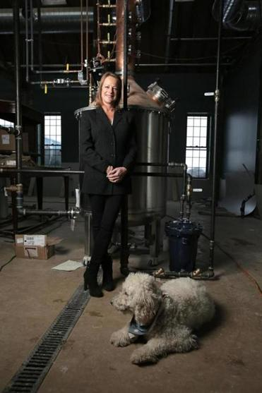 Rhonda Kallman and her dog Sandy, at the Boston Harbor Distillery, which is under construction in a Civil War-era complex in Dorchester.