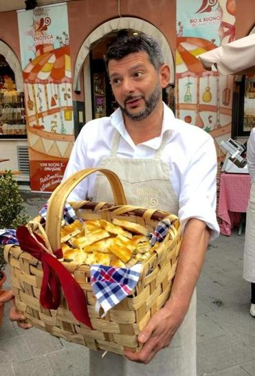 10travitaly - Guido Porrati, 4th generation owner of family's cured meat business, Parla Come Mangi, in Rapallo, Italy. He greets guests w a basket of focaccia. (Sheryl Julian/Globe Staff)