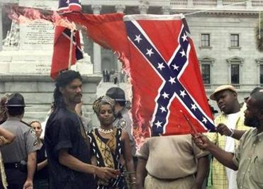 In this May 10, 2000, photo, demonstrators burned the Confederate flag in Columbia, S.C., to protest the Confederate flag flying at the South Carolina Statehouse.
