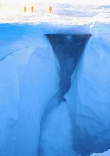 Obervers stood in 2013 above melting water on part of the glacial ice sheet that covers about 80 percent of Greenland.